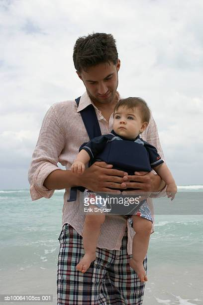 father carrying baby daughter (15-18 months) on beach - strap stock pictures, royalty-free photos & images