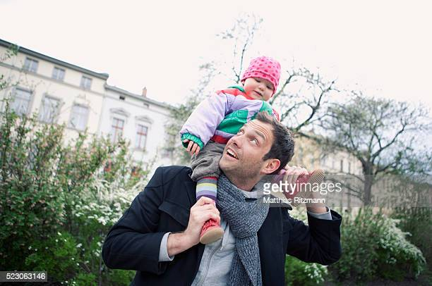 father carrying baby daughter (6-12 months) on shoulders - human joint stock pictures, royalty-free photos & images
