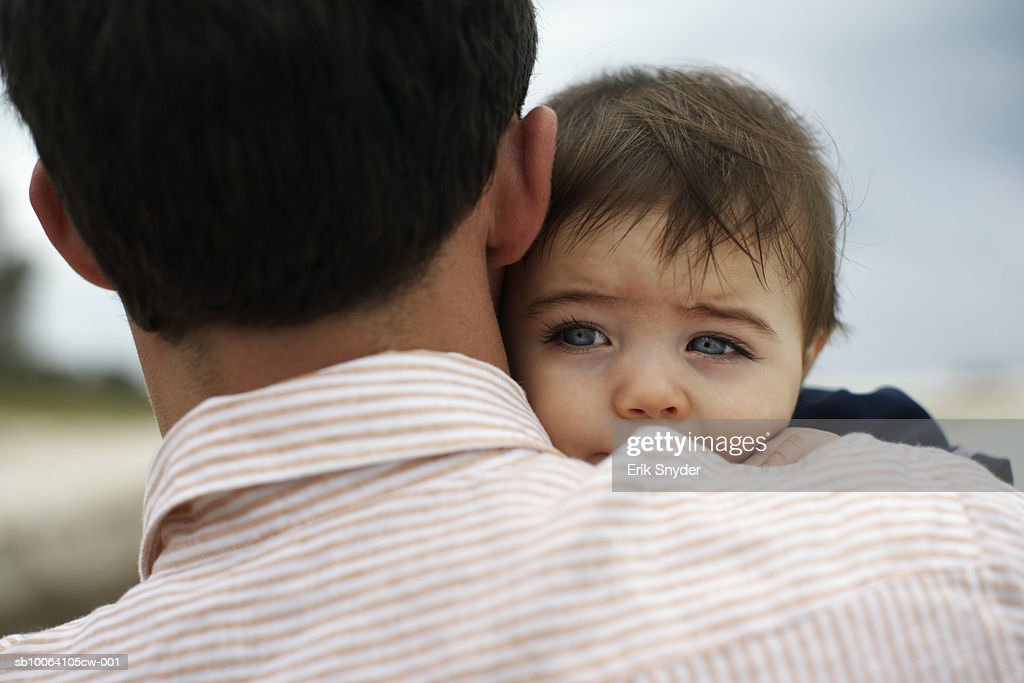 Father carrying baby daughter (15-18 months) outdoors, close-up : Stock Photo