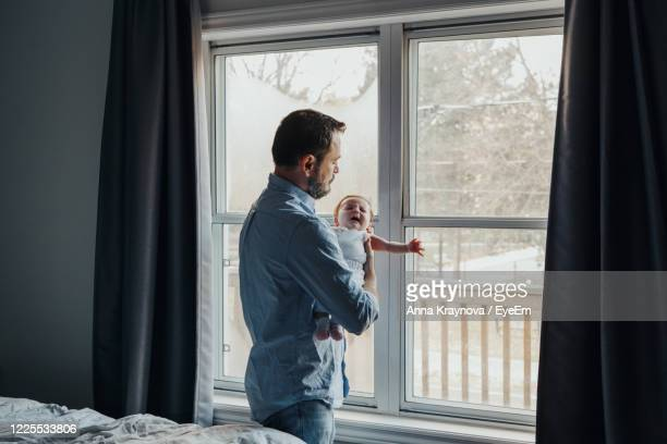 father carrying baby daughter while standing by window at home - genderblend stock pictures, royalty-free photos & images