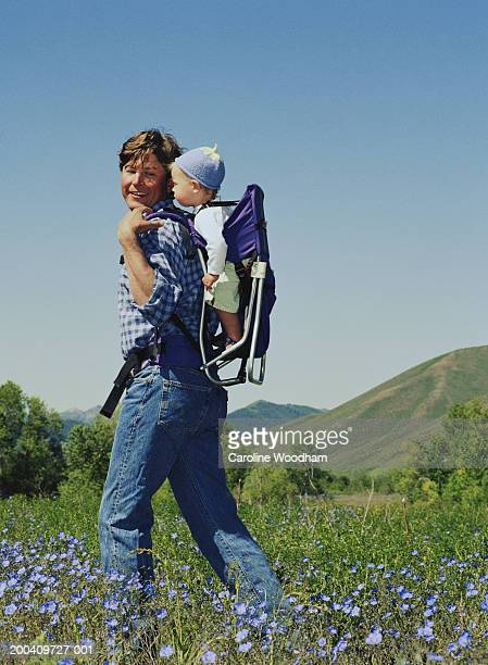 father carrying baby girl (6-9 months) on back in field, smiling - ketchum idaho stock photos and pictures
