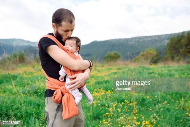 Father carrying baby girl outdoors in a baby sling
