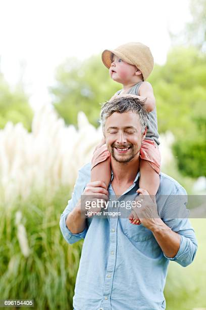 Father carrying baby son on shoulders