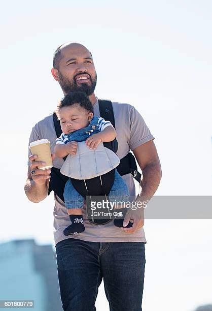 Father carrying baby son outdoors