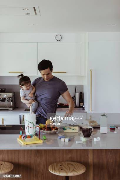 father carrying baby son while preparing food in kitchen - stay at home father stock pictures, royalty-free photos & images
