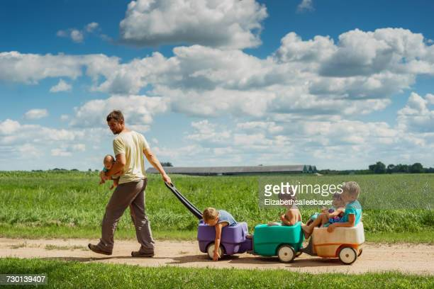 father carrying baby son while pulling four children in a wagon - large family stock pictures, royalty-free photos & images