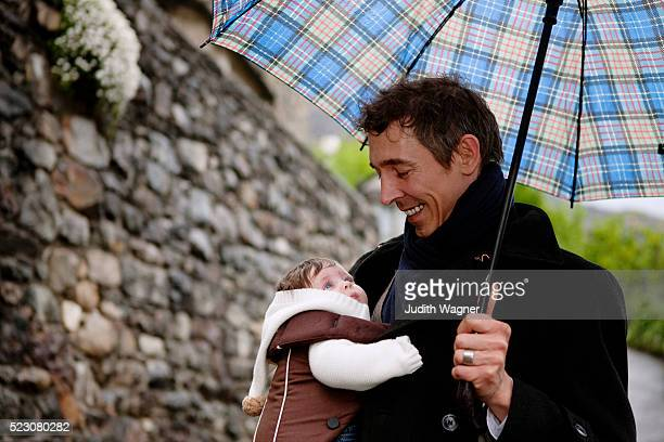 Father carrying baby (2-5 months) under umbrella