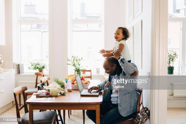 father carrying cheerful daughter on shoulder while working on laptop at table in house - working from home stock pictures, royalty-free photos & images