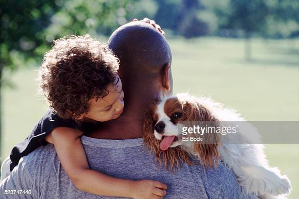 father carrying child and dog - cavalier king charles spaniel stock pictures, royalty-free photos & images