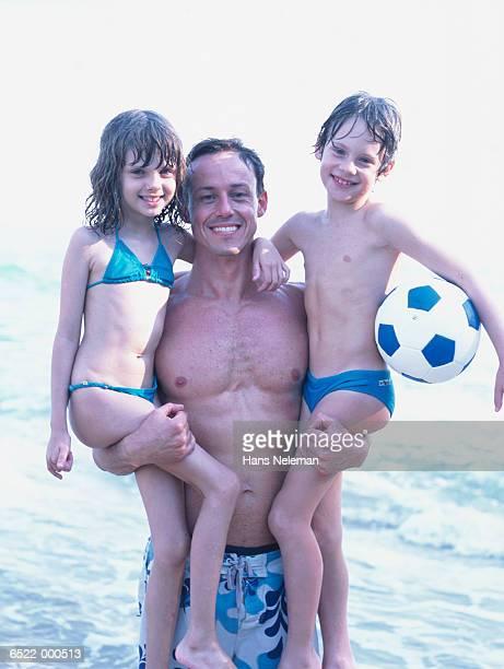 father carrying children - knaben in badehosen stock-fotos und bilder