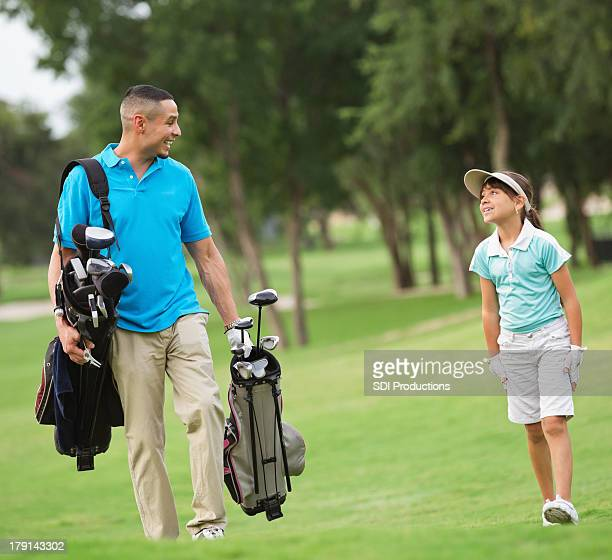 Father carrying clubs for daughter while playing golf together
