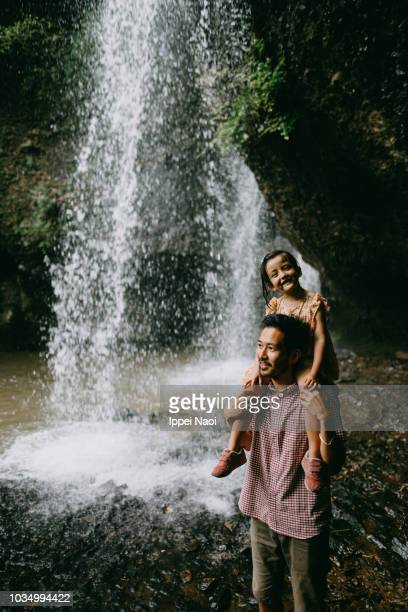 Father carrying cute little girl piggyback under waterfall, Japan