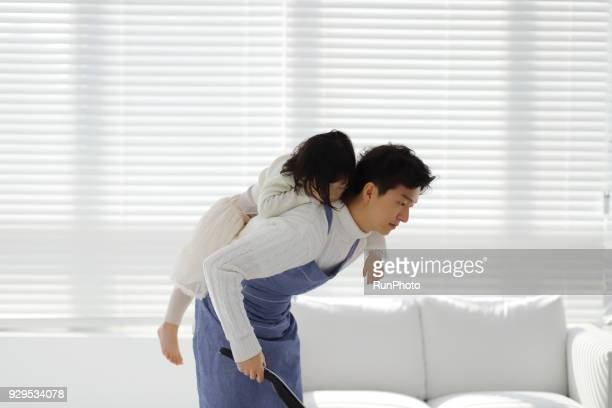 Father carrying daughter and vacuuming