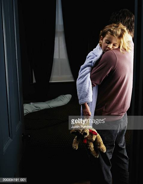Father carrying daughter (6-8), daughter holding teddy bear
