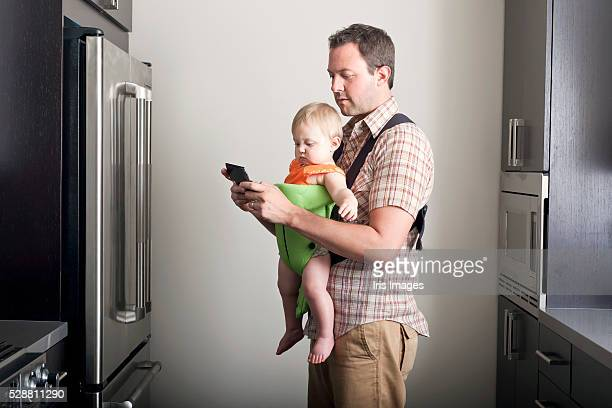 Father carrying daughter (6-12 months) in carrier and text messaging