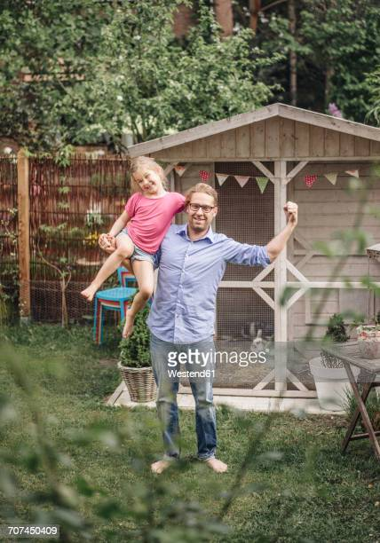 Father carrying daughter in garden