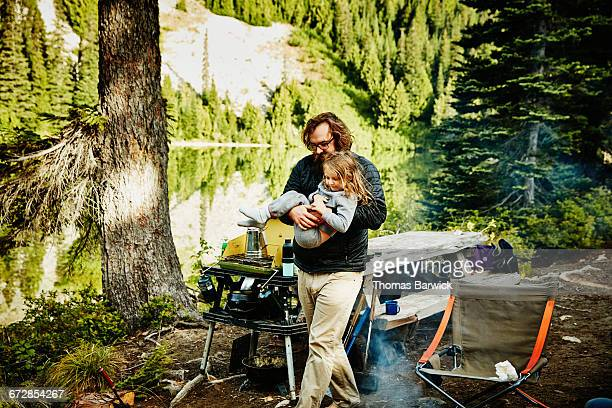 Father carrying daughter in pajamas while camping