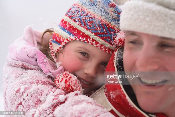 father carrying daughter on back in snow, portrait, close-up - peter snow stock pictures, royalty-free photos & images