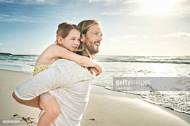 Father carrying daughter on beach