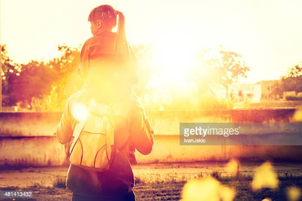 father carrying daughter on his shoulders in city at sunset - carrying a person on shoulders stock photos and pictures