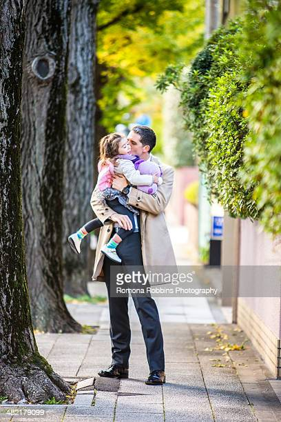 Father carrying daughter on pavement