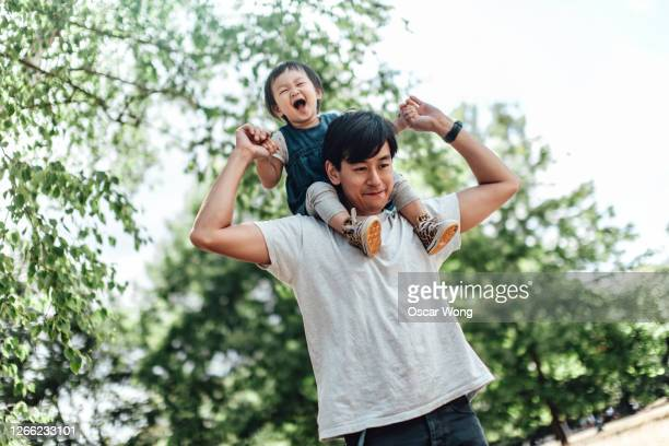 father carrying daughter on shoulder at the park - genderblend stock pictures, royalty-free photos & images