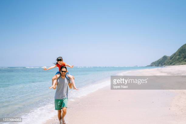 father carrying daughter on shoulders and running on tropical beach - climate stock pictures, royalty-free photos & images