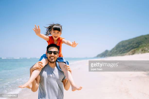 father carrying daughter on shoulders and running on tropical beach - 鹿児島県 ストックフォトと画像