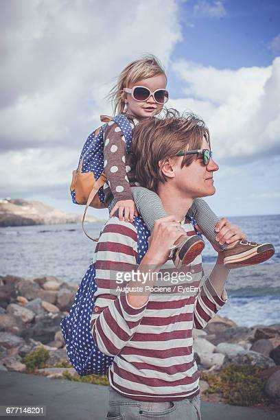 father carrying daughter on shoulders at shore against sky - leanintogether stock pictures, royalty-free photos & images