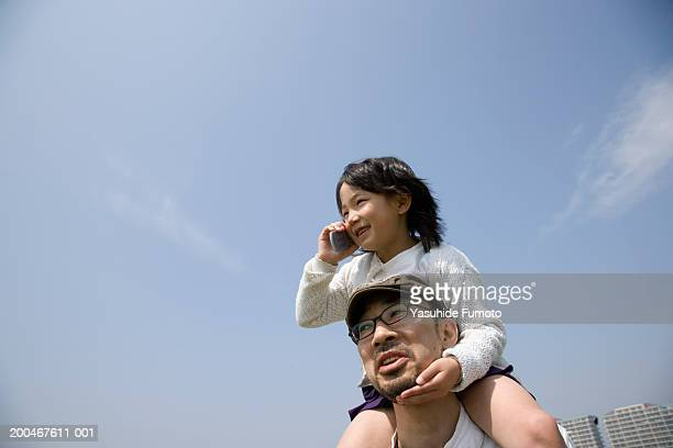 father carrying daughter (7-9) on shoulders, girl using cell phone - carrying a person on shoulders stock photos and pictures