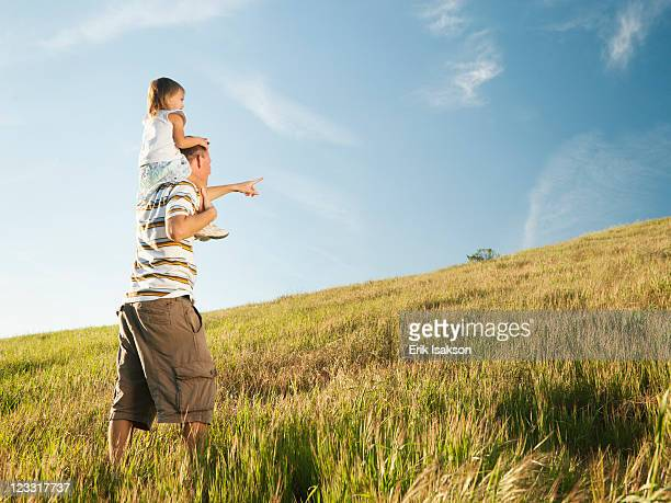 Father carrying daughter on shoulders in field