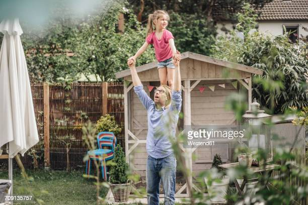Father carrying daughter on shoulders in garden