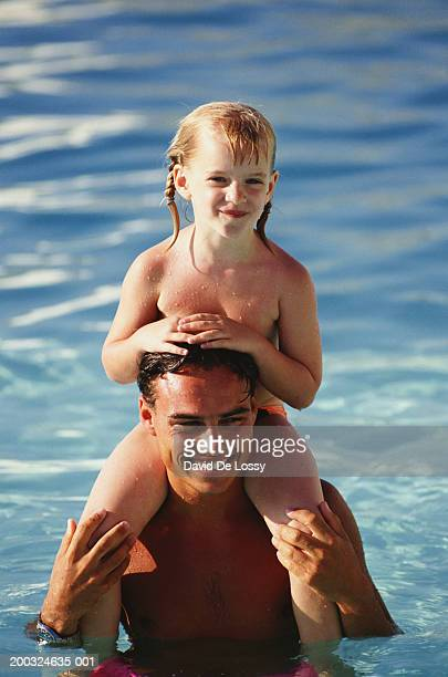 father carrying daughter (6-7) on shoulders in pool, close-up - wet girl stock photos and pictures