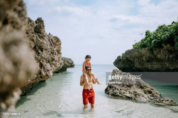 father carrying daughter on shoulders in tropical beach water - ippei naoi stock pictures, royalty-free photos & images