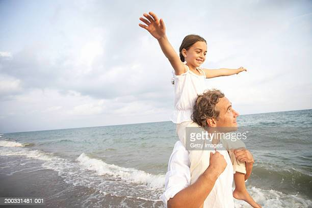 Father carrying daughter (6-8) on shoulders, on beach, arms raised