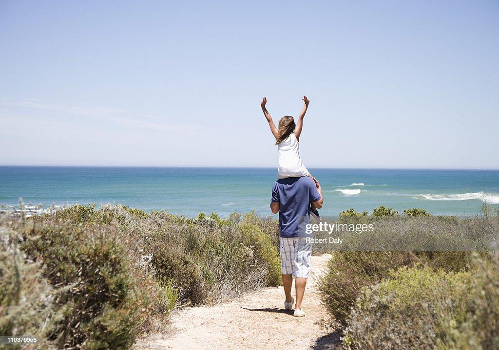 Hija de padre llevar en hombros en la playa ruta : Foto de stock