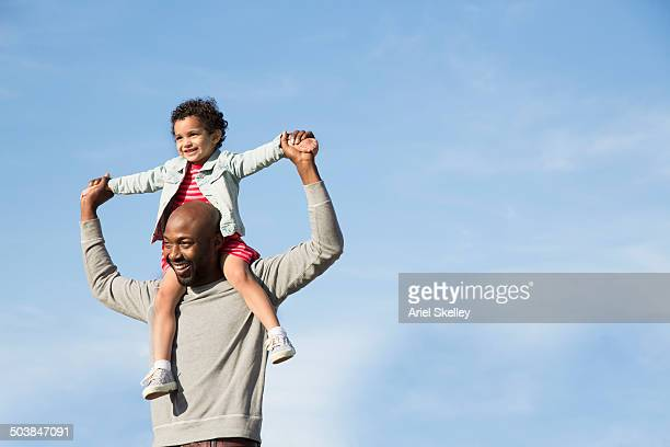 father carrying daughter on shoulders outdoors - carrying on shoulders stock pictures, royalty-free photos & images