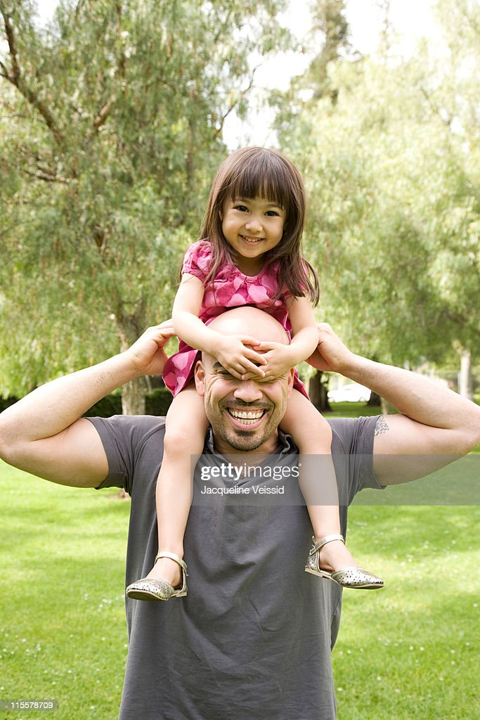 Father carrying daughter on shoulders : Stock Photo