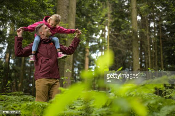 father carrying daughter on shoulders. - reality fernsehen stock pictures, royalty-free photos & images