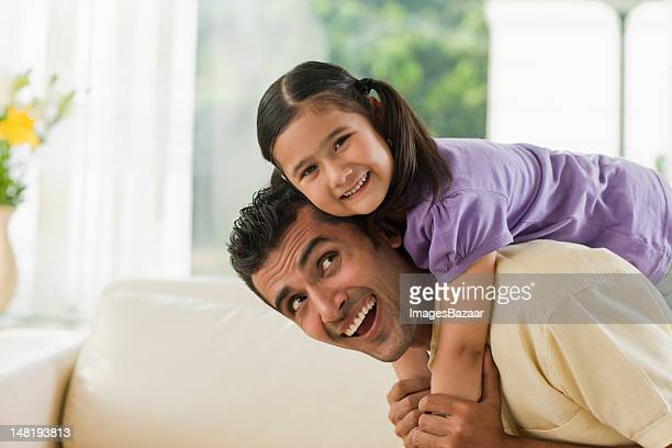 Father carrying daughter (6-7) on shoulders