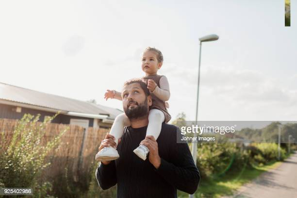 father carrying daughter on shoulders - shoulder stock pictures, royalty-free photos & images