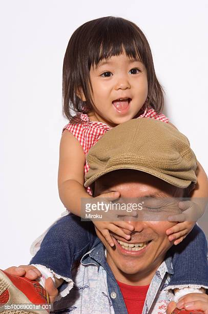 father carrying daughter (2-3) on shoulders, smiling, close-up - flat cap stock photos and pictures