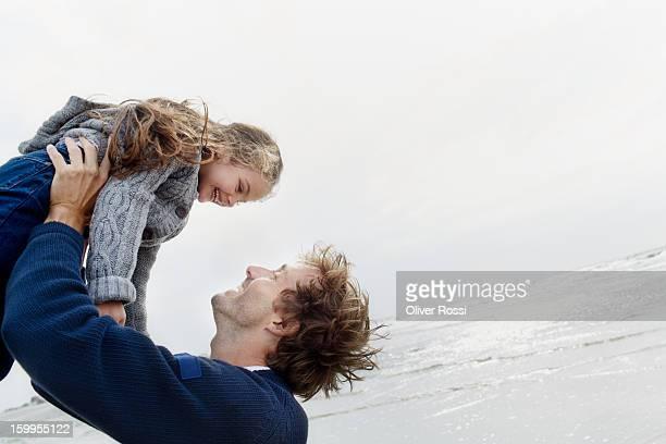 father carrying daughter on the beach - schrägansicht stock-fotos und bilder