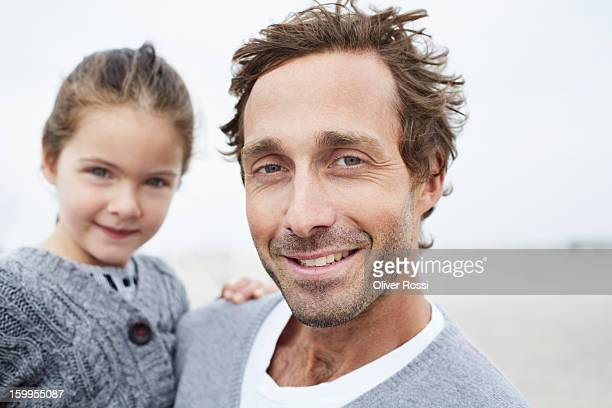 father carrying daughter on the beach, portrait - mid adult men stock pictures, royalty-free photos & images