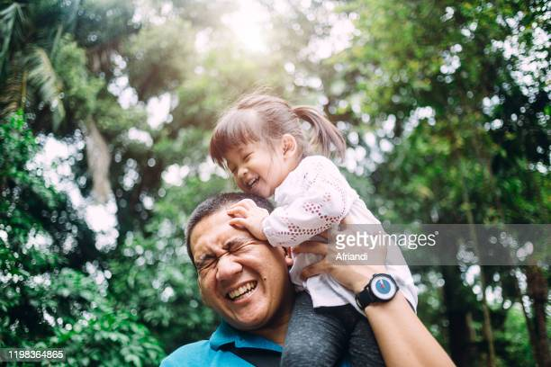 father carrying daughter on the shoulder - indonesia stock pictures, royalty-free photos & images