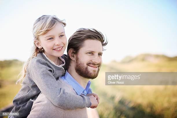 Father carrying daughter piggyback at the coast