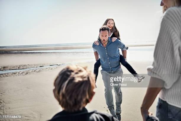 father carrying daughter piggyback on the beach - travel stock-fotos und bilder