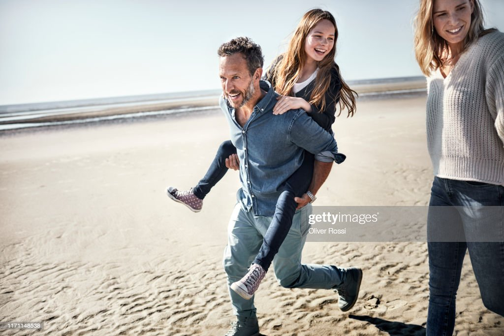 Father carrying daughter piggyback on the beach : Stock-Foto