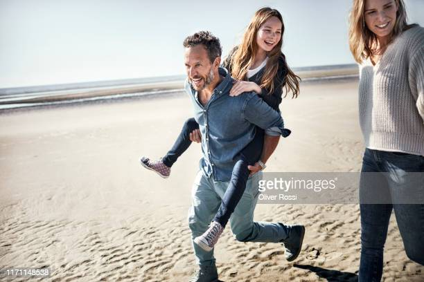 father carrying daughter piggyback on the beach - bewegung stock-fotos und bilder