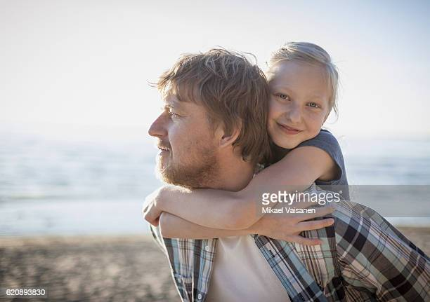 Father carrying daughter piggyback on the beach